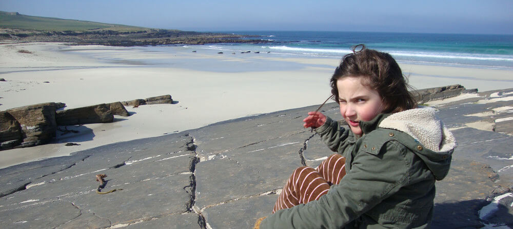 Our daughter watching the seals play in the sea, Sandy, Orkney in the Northern Isles