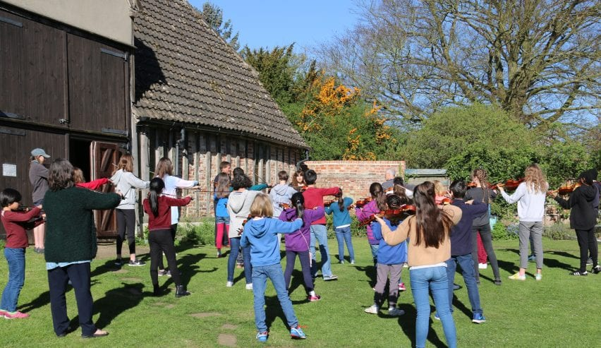 Musicians in the garden at historic Tudor Barn Hostel at Milden Hall, nr Lavenham, Suffolk