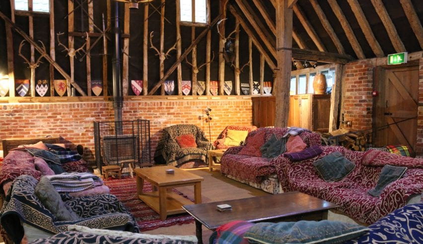 Seating area around woodburner at historic Tudor Barn Hostel at Milden Hall, nr Lavenham, Suffolk
