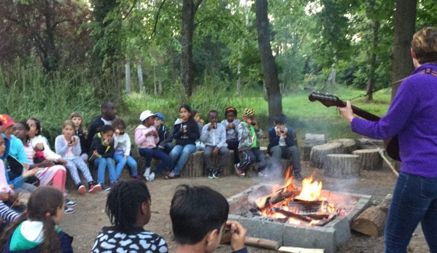 School group campfire fun at Gaveston Hall group hostel near Horsham, West Sussex just 1 hour from London