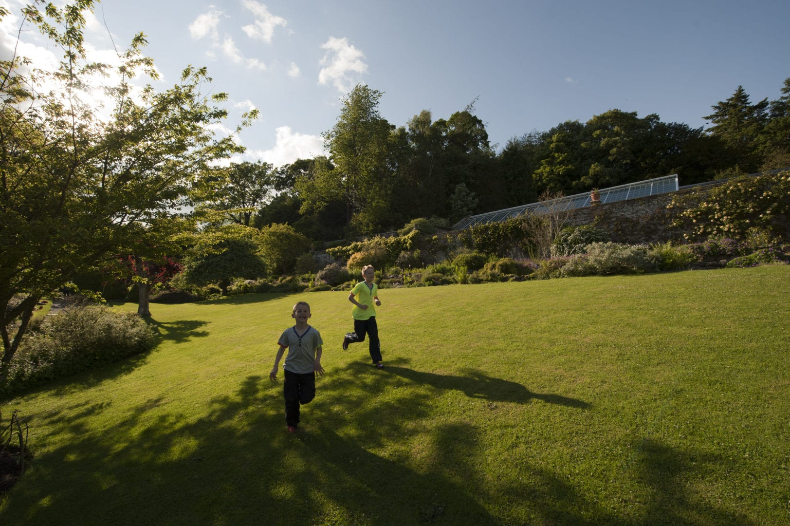 Children playing in the garden at Wallington Bunkhouse, Northumberland.