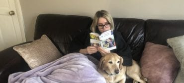Girl and dog read the Independent Hostel Guide on a sofa