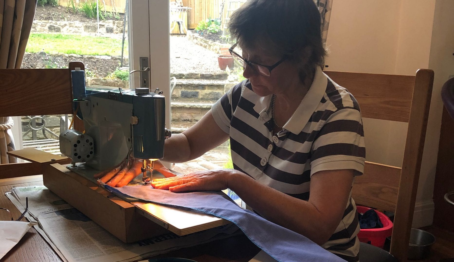 volunteer ferlouged staff from independent hostels UK sewing scrubs on a sewing machine