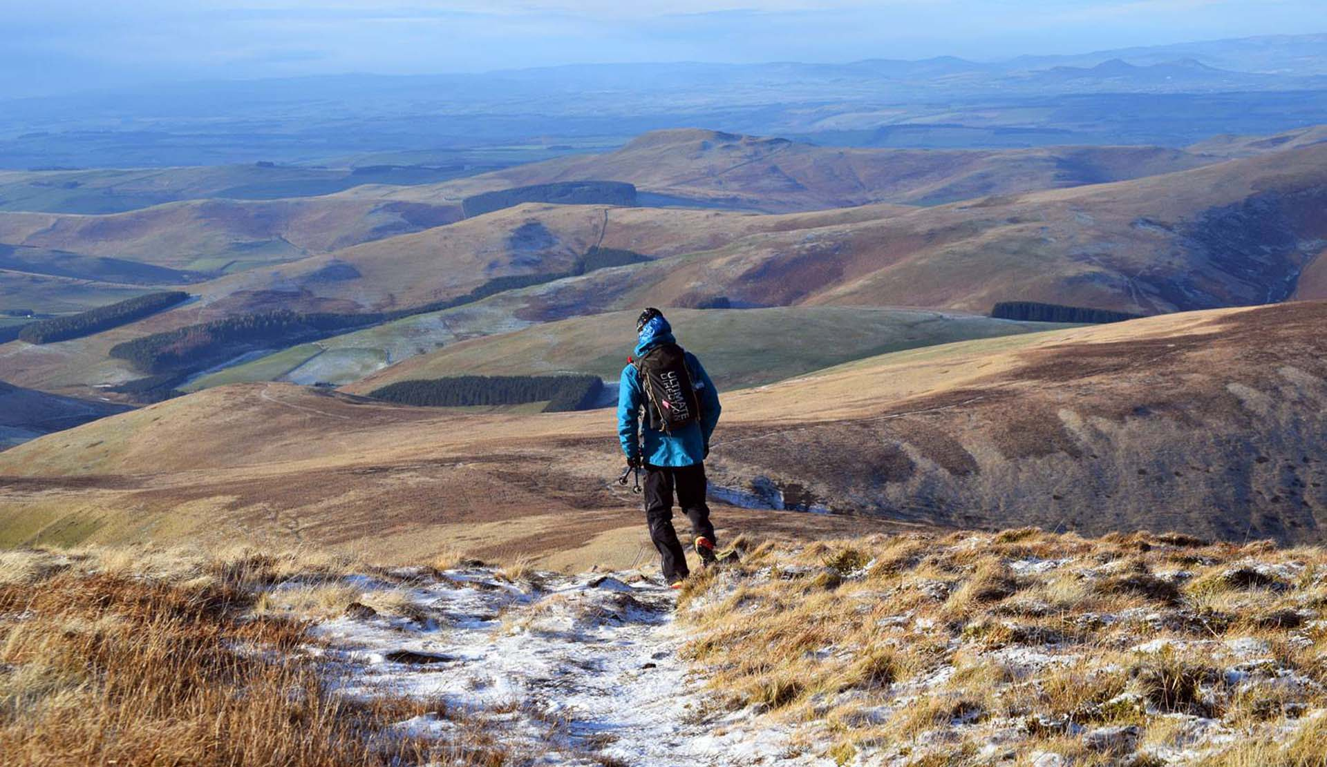 Walker in a winter scene on the northumberland hills above Wooler Hostel