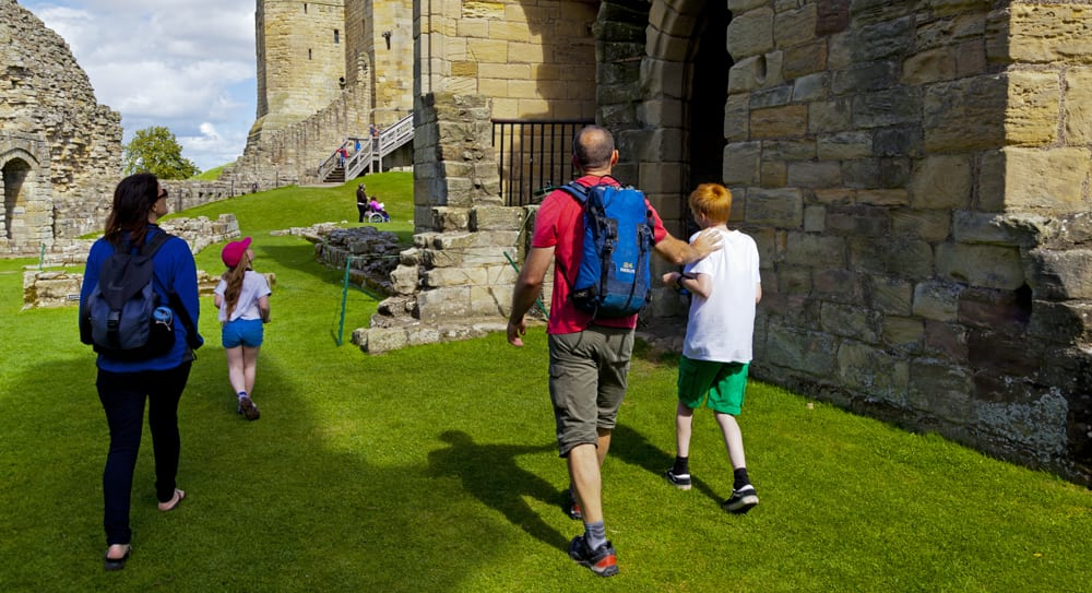 family explore castle in northumberland