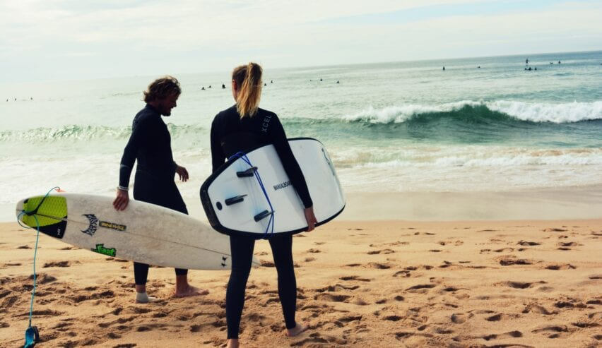 Two people on the beach going surfing