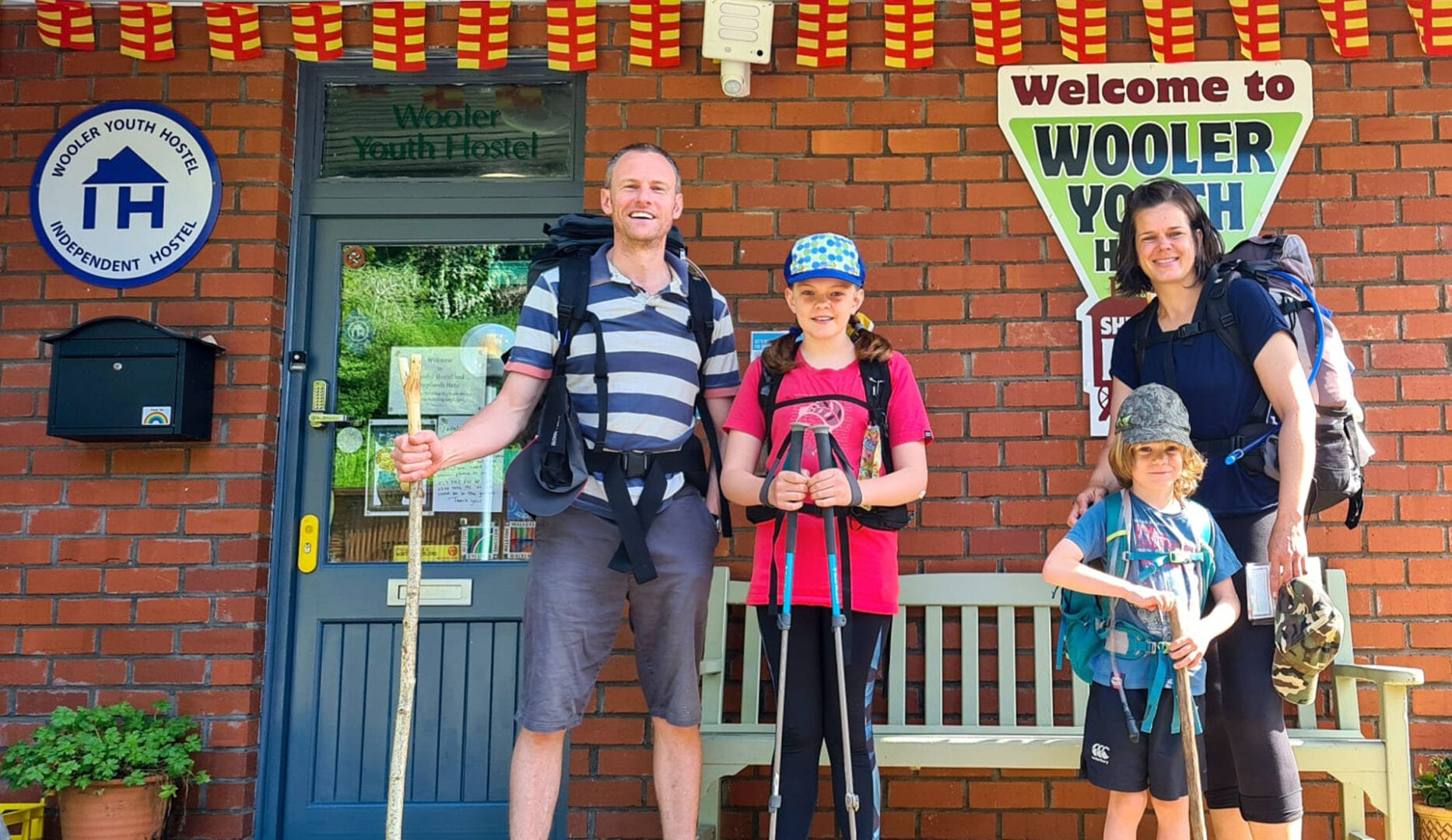 family at wooler youth hostel with independent hostels sign