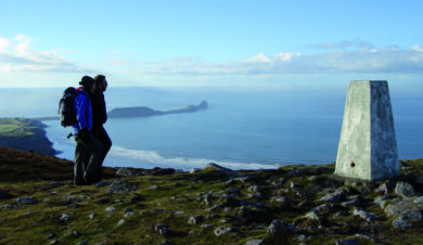 Walkers at trip point overlooking Rhossili bayon the Gower Penisular