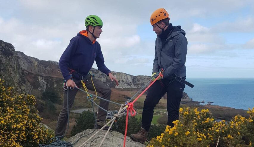 climbing near walkers on cliff by beach by Anglesey Outdoor Centre