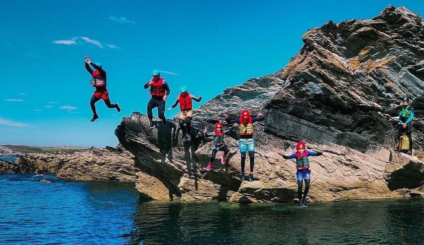 coasteering at climbing near walkers on cliff by beach by Anglesey Outdoor Centre